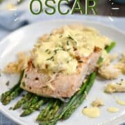Salmon filet on a bed of asparagus spears topped with crab and a creamy sauce. with title graphic across the top