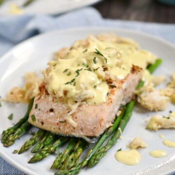 grilled salmon on a bed of asparagus topped with lump crab and bernaise sauce on an off-white plate with a second plate in the background