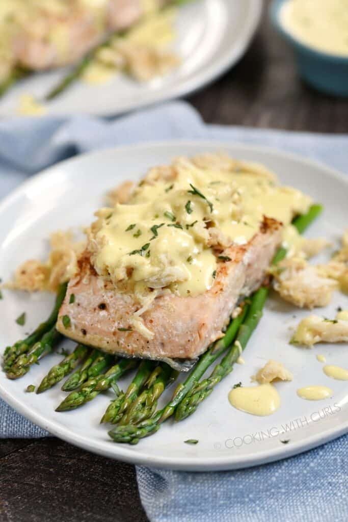 grilled salmon on a bed of asparagus topped with lump crab and bernaise sauce on an off-white plate with a second plate in the background.