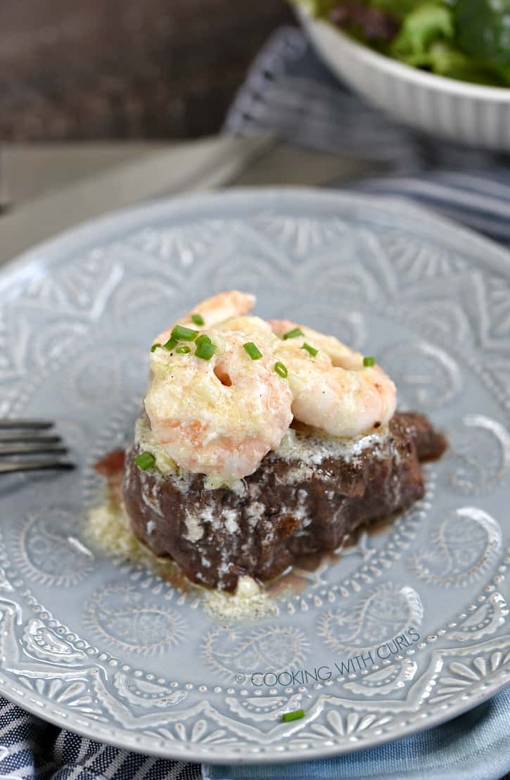 shrimp topped filet sitting on a gray plate