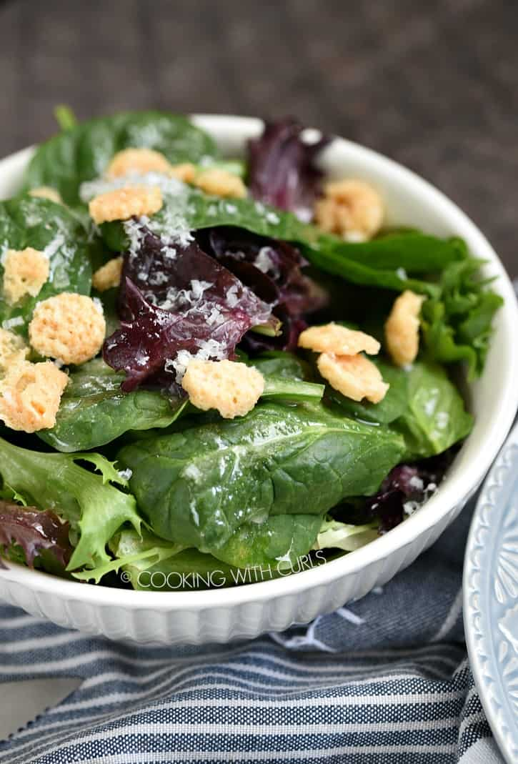 Spring Mix Salad with citrus vinaigrette and parmesan crisps in a small white bowl