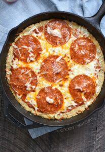 a blue napkin on a wooden board topped with a cast iron skillet pepperoni pizza