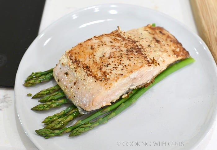 cooked salmon filet on a bed of asparagus on a small off-white plate