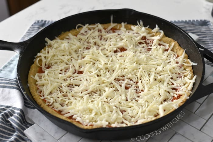 shredded cheese covering the pizza sauce and keto crust in a cast iron skillet
