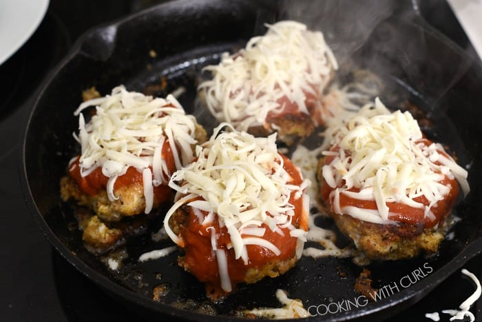 top the Parmesan crusted chicken breasts with tomato sauce and shredded mozzarella cheese in the skillet