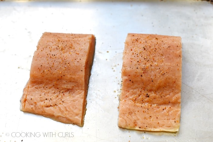 two salmon filets on a baking sheet sprinkled with garlic pepper