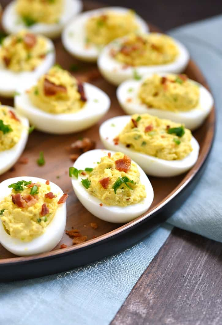 bacon ranch deviled eggs on a wooden plate sitting on a blue napkin