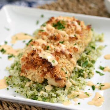 Macadamia Nut Crusted Mahi-Mahi drizzled with Sweet Chili Lime Butter Sauce on a bed of cauliflower rice on a white, square plate
