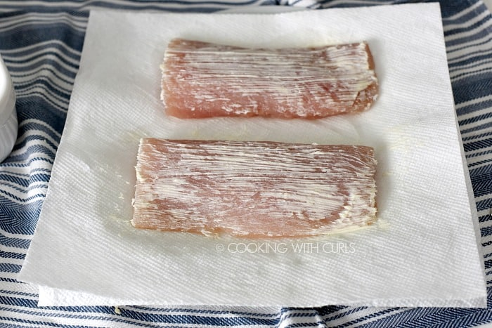 Mahi mahi filets brushed with butter sitting on paper towels