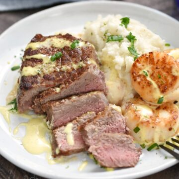 Sliced steak nestled into mashed cauliflower and seared scallops drizzled with lime-dill hollandaise on a white plate