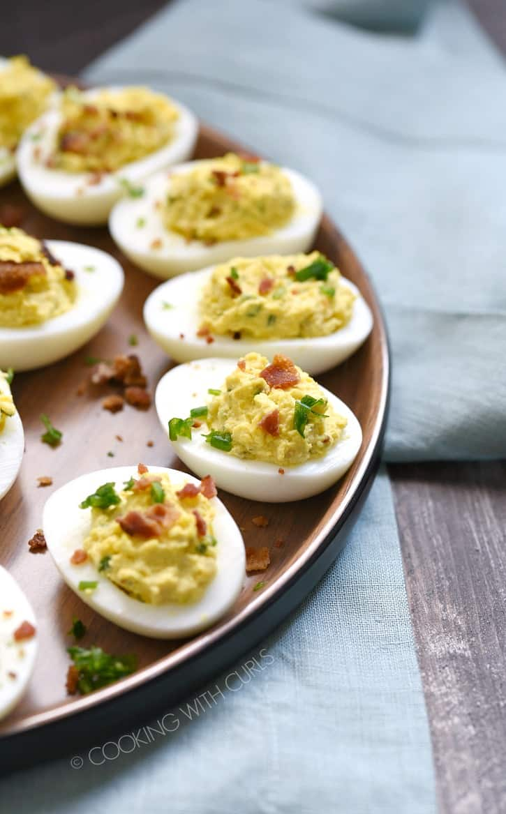 a wooden plate holding bacon ranch deviled eggs sitting on a blue napkin on a wooden board