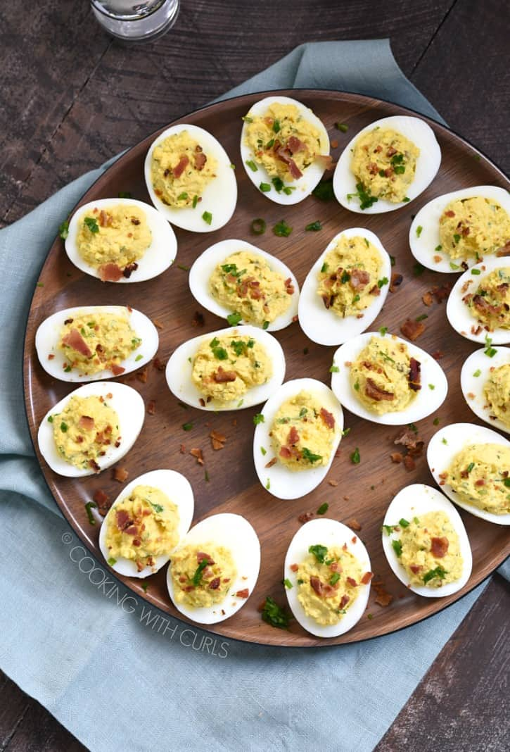 a large wooden plate holding bacon ranch deviled eggs sprinkled with green onions and sitting on a blue napkin