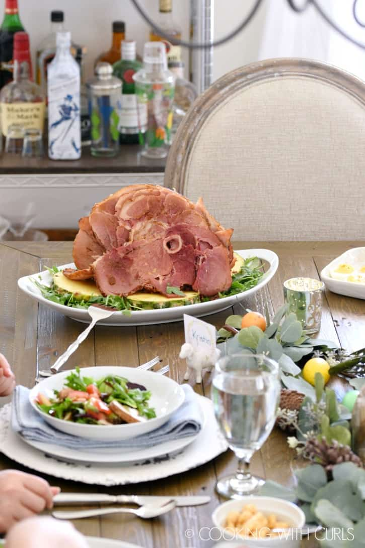 a holiday table with bowls of salad, a platter with deviled eggs and a large oval platter holding a spiral cut ham