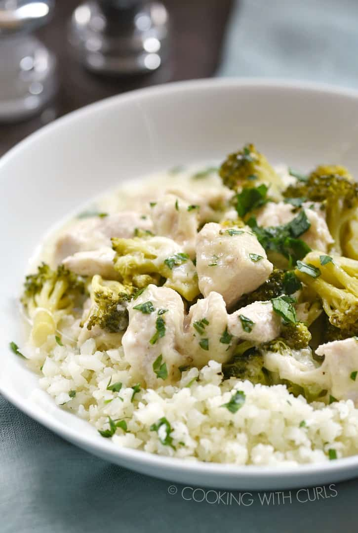 chopped chicken and broccoli in a cheese sauce served over cauliflower rice in a white bowl