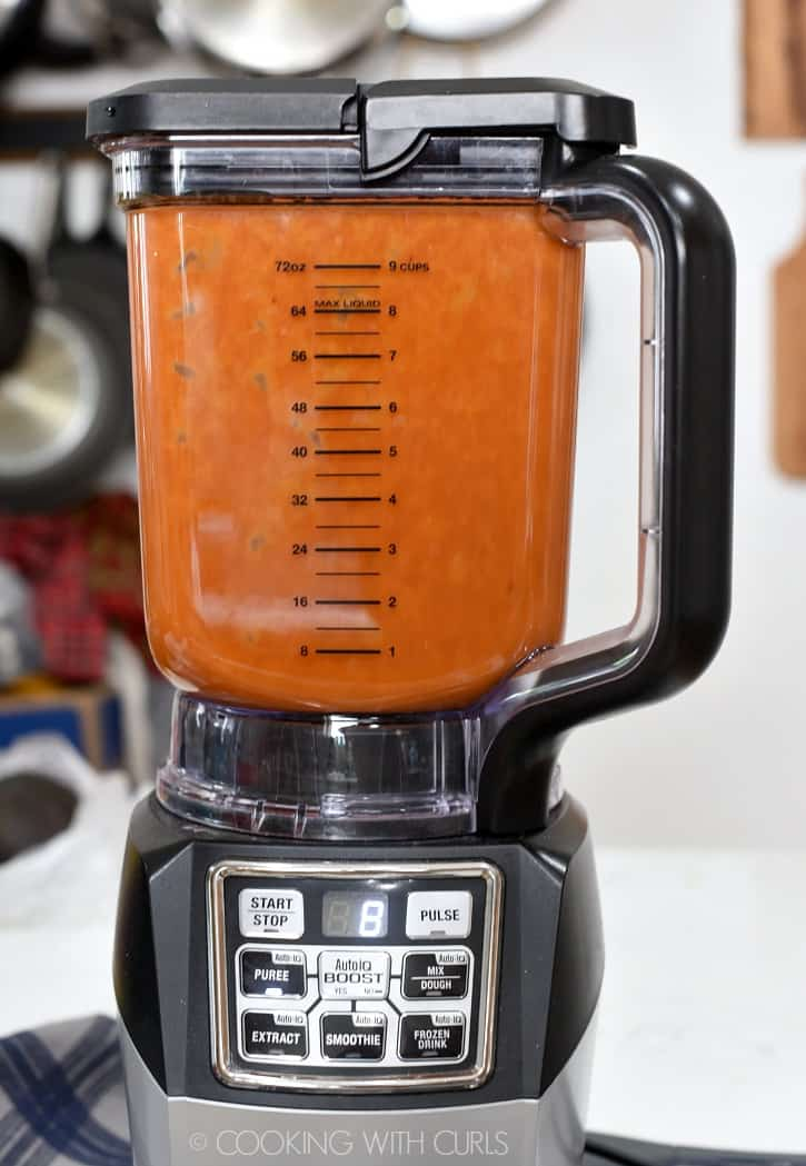 A blender sitting on a white counter blending the ingredients to make homemade french dressing