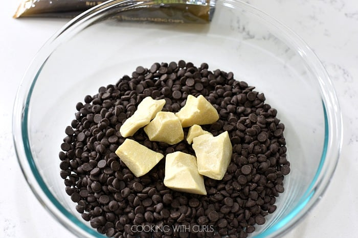 A clear bowl with chocolate chips and chunks of cocoa butter sitting on a marble counter with a bag of chocolate chips in the background