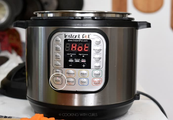 A pressure cooker set to Saute and HOT on the display