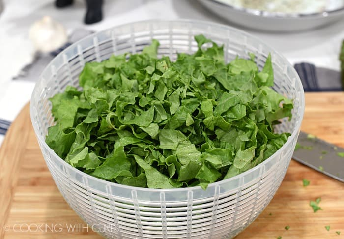 A white spinner basket filled with chopped lettuce leaves sitting on a wood cutting board
