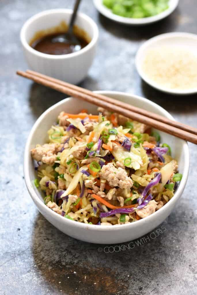 egg roll in a bowl with wood chop sticks resting on the bowl. Small white bowls with teriyaki sauce, green onions and sesame seeds are in the background