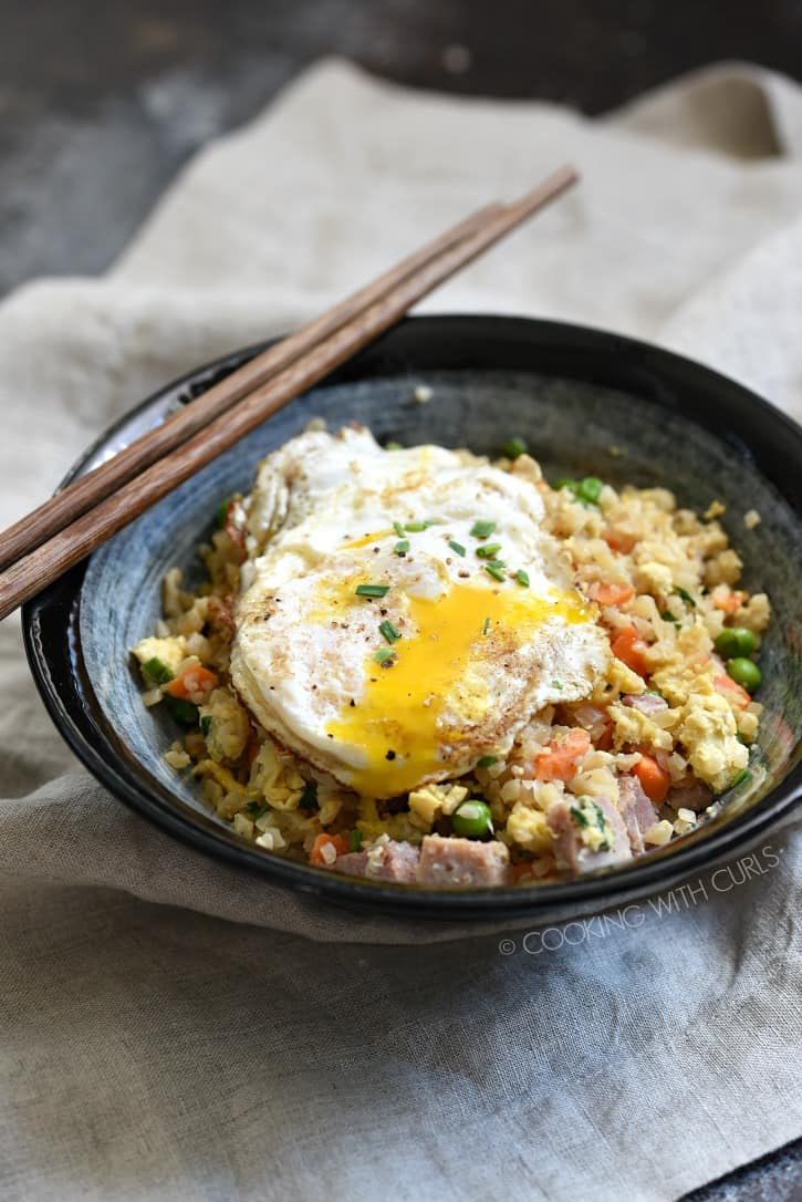 a dark blue bowl with ham fried rice and a fried egg with wood chop stick on the edge of the bowl, all sitting on a beige napkin
