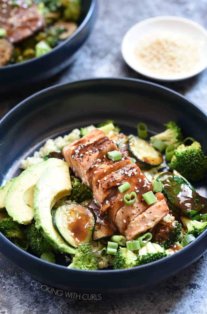 two blue bowls filled with vegetables and topped with salmon, teriyaki sauce, green onions and avocado. two small bowls with toasted sesame seeds and green onions are in the background