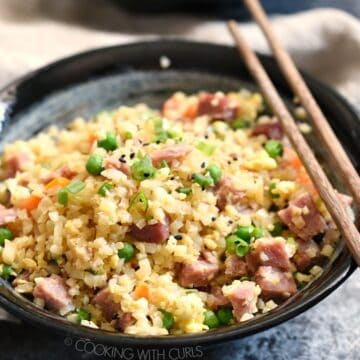 two bowls of ham fried rice with wood chop sticks on the edge of the bowl and a beige napkin between the bowls