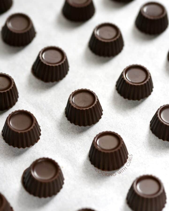 small dark mint chocolate fat bombs lined up on a piece of white parchment paper