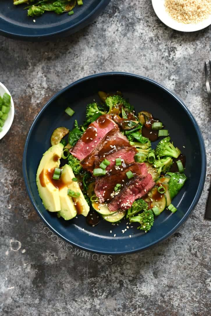 a dark blue bowl filled with vegetables and topped with sliced steak, teriyaki sauce and green onions