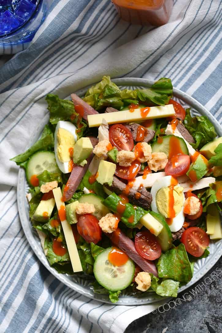 A blue and white striped napkin holds a plate covered with lettuce, cheese, hard boiled egg wedges, cherry tomatoes and assorted meats cut into strips to create the perfect Chef's Salad