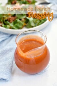 Homemade French Dressing in a clear glass pitcher with a blue napkin and plate of salad in the background