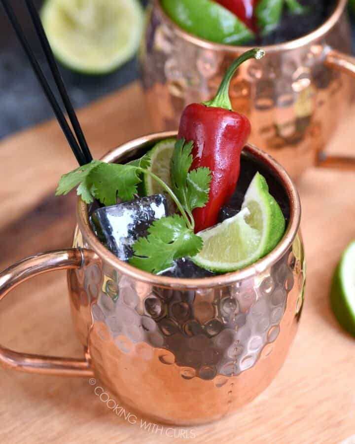 two copper mugs sitting on a wooden board filled with ice cubes, lime juice, tequila and ginger ale. They are topped off with a squished lime wedge, sprig of cilantro and a red chile pepper