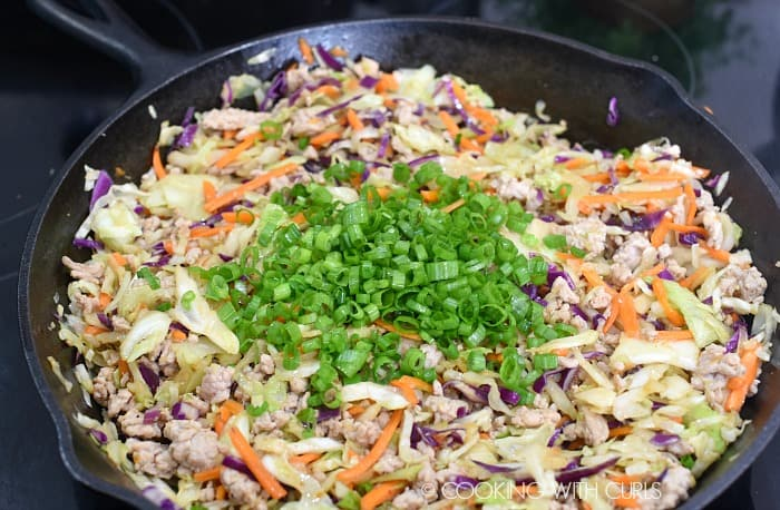 chopped green onions added to the shredded cabbage and ground pork in the cast iron skillet