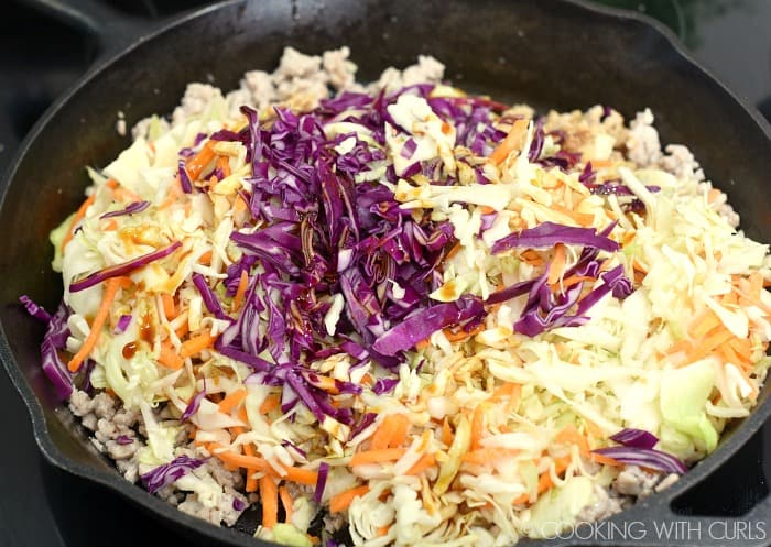 shredded cabbage and ground pork in a cast iron skillet