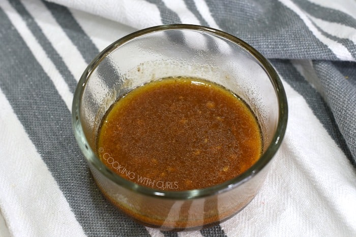 Cooking liquid mixed with thickener in a small glass bowl