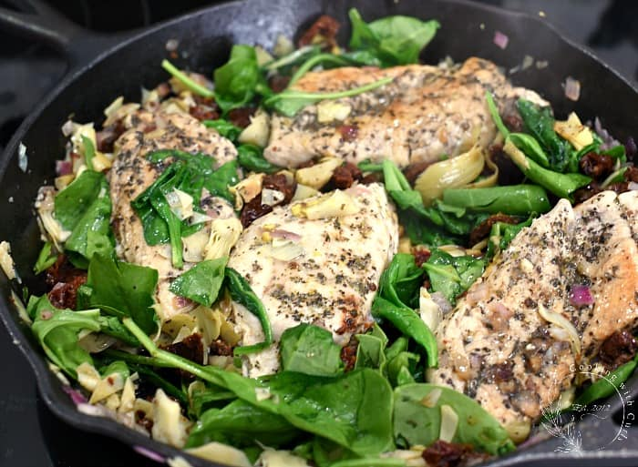 Four chicken breasts topped with sun-dried tomatoes, artichoke hearts and wilted spinach in a cast iron skillet
