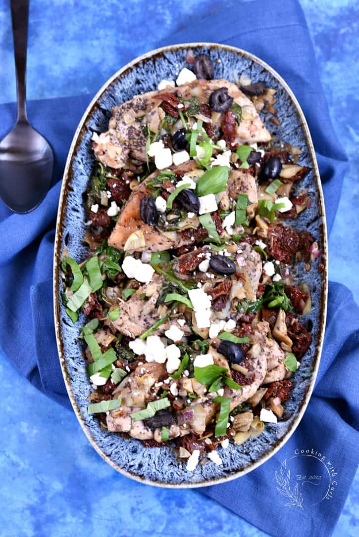 Mediterranean Chicken topped with sun-dried tomatoes, artichoke hearts, Feta cheese, black olives, spinach and lemon juice in an oval blue bowl on a bright blue background