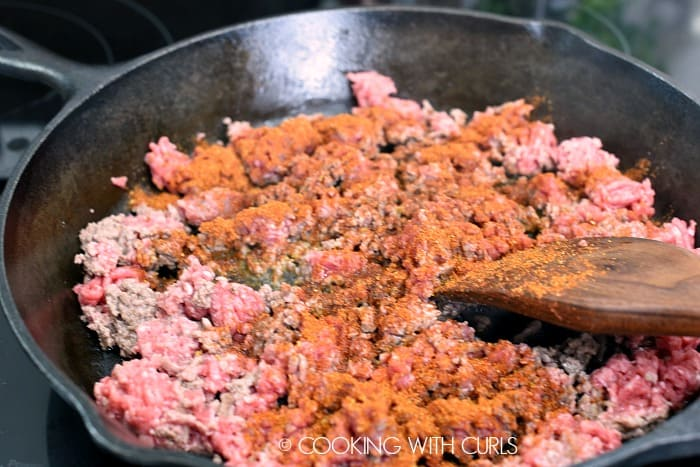 Taco seasoning sprinkled over ground beef in a cast iron skillet with a wooden spatula in the bottom corner