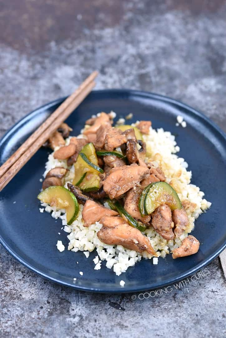 Instant Pot Chinese Garlic Chicken served over rice on a blue plate with wooden chopsticks in the upper right hand corner