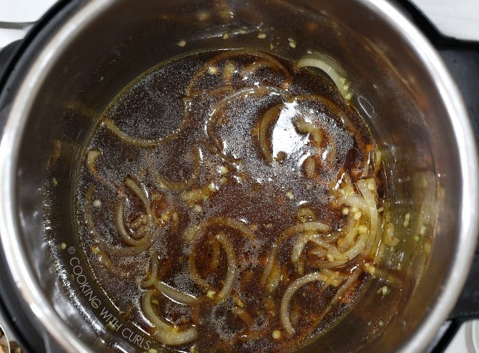 Thinly sliced onions, garlic, soy sauce and chicken stock in the metal liner of a pressure cooker