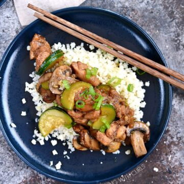 Instant Pot Chinese Garlic Chicken served over a bed of cauliflower rice, served on a blue plate with wooden chopsticks laying in the upper right hand corner of the plate