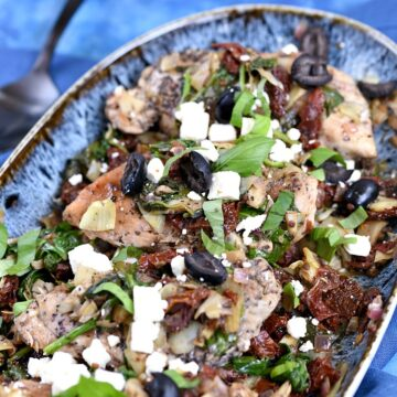 Chicken breasts topped with artichoke, tomato, olives, feta and basil in a blue bowl on a blue background