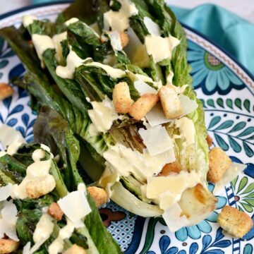 Grilled romaine lettuce topped with Caesar dressing, shaved Parmesan and croutons on a large platter