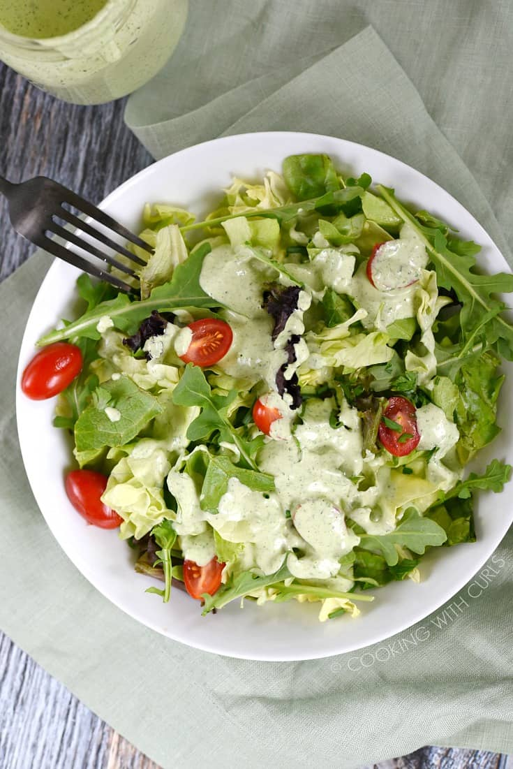 A bowl of salad greens and sliced tomatoes topped with Green Goddess Dressing.