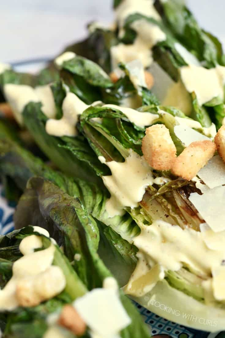 A close up shot of Grilled Caesar Salad with dressing and croutons