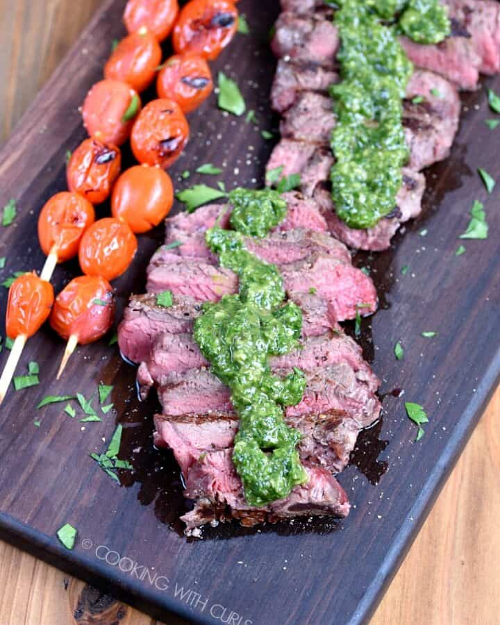 Sliced Sirloin Steak topped with Chimichurri sauce on a wooden cutting board with skewered tomatoes on the side.