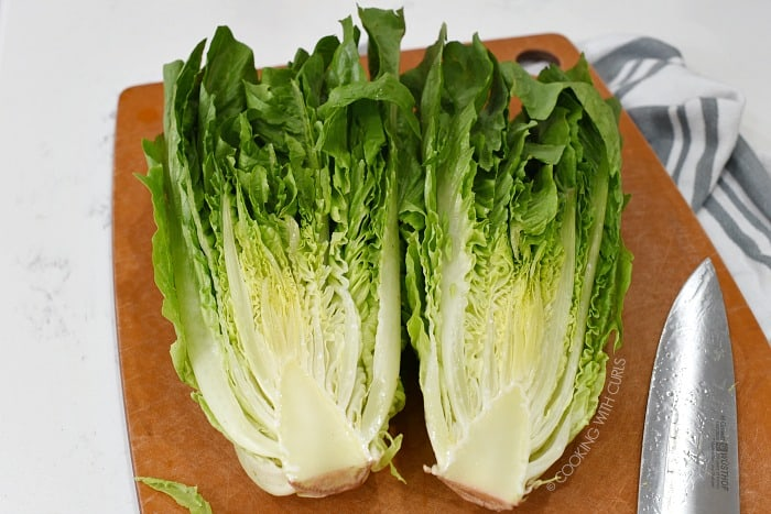 Slice romaine lettuce in half on a cutting board with a sharp knife