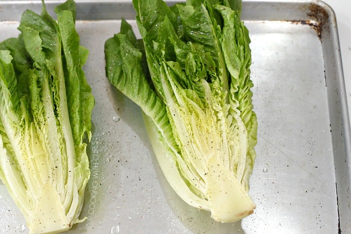 Washed romaine lettuce halves on a baking sheet topped with oil, salt and pepper