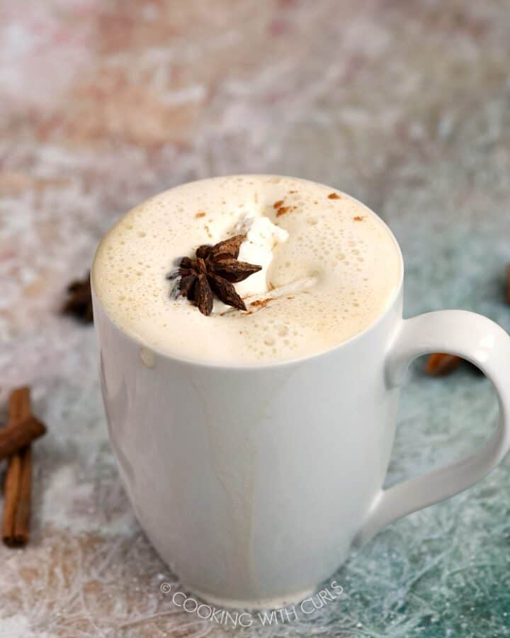 A Pumpkin Spice Latte in a white mug topped with whipped cream