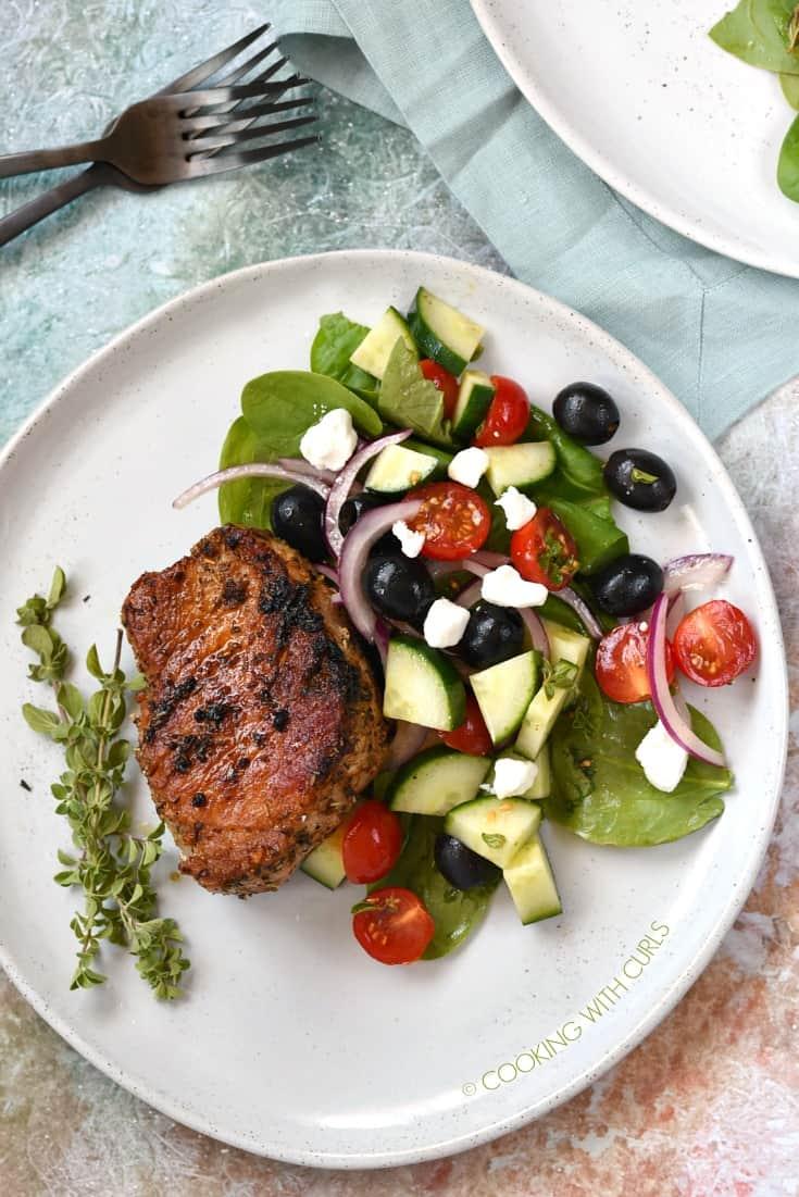 Greek Pork Chops with a Greek side salad and fresh oregano sprigs