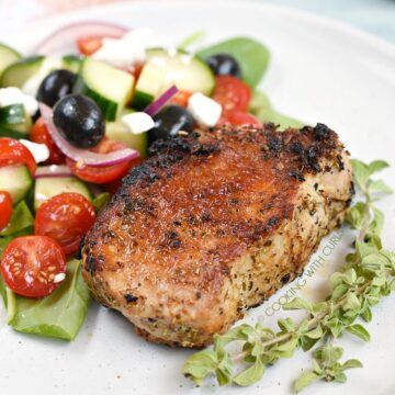 Boneless, Greek Pork Chops served with a Greek salad and sprigs of fresh oregano